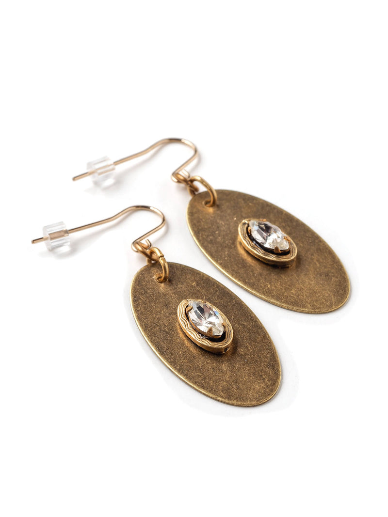 Three quarter closeup view of modern oval drop earrings in antique gold with rhinestone navette accents