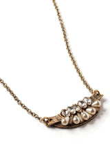 closeup view of short and petite mini-bib style necklace in antique gold with teardrop pearls, rhinestone navettes, and glass bugle beads