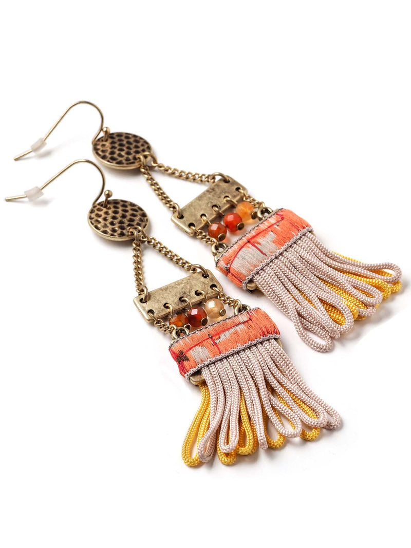 closeup view of ladder style earrings with ribbon detail and tassels