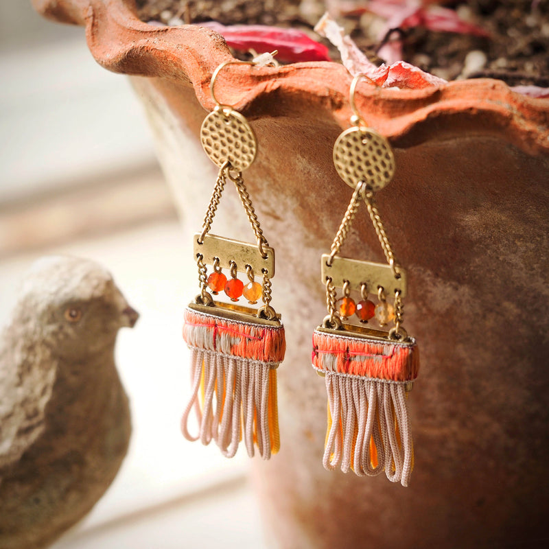 ladder earrings with tassels are hanging off the edge of a terracotta pot