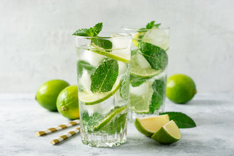 Image of two mojitos filled with lime slices and mint leaves