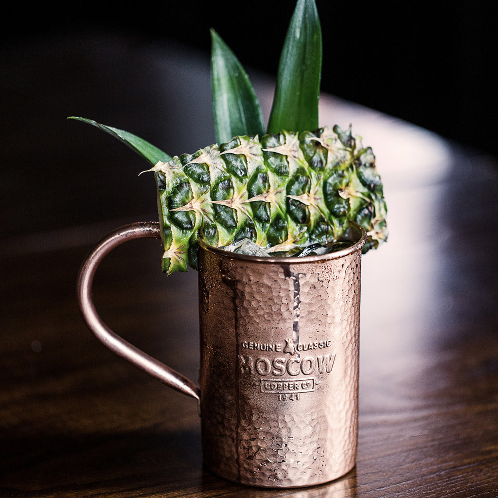 A spear of fresh pineapple is the perfect garnish for a Moscow Copper Co. hammered copper mug.