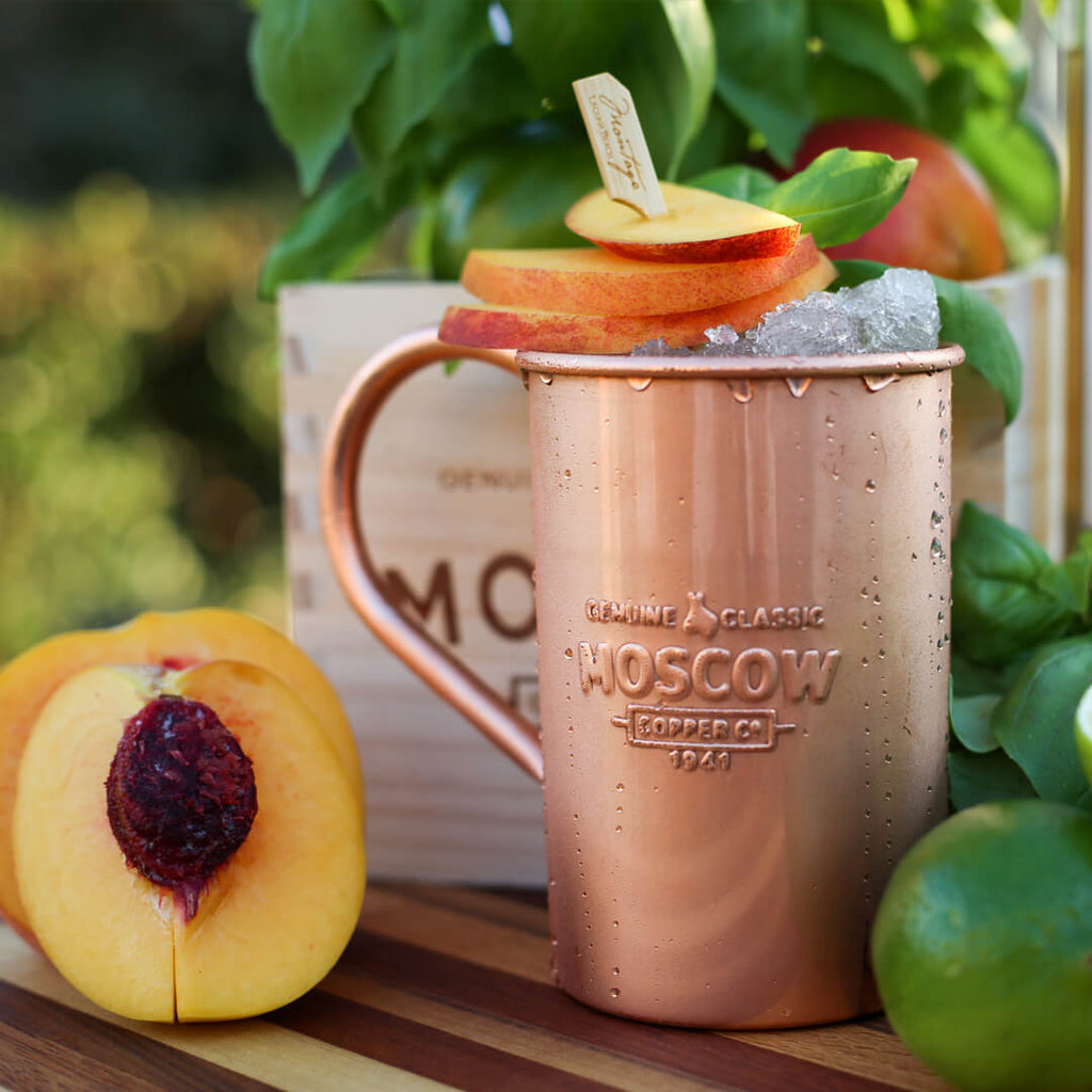 Fresh peaches liven up the typical Moscow Mule, served in a 100% pure copper mug.