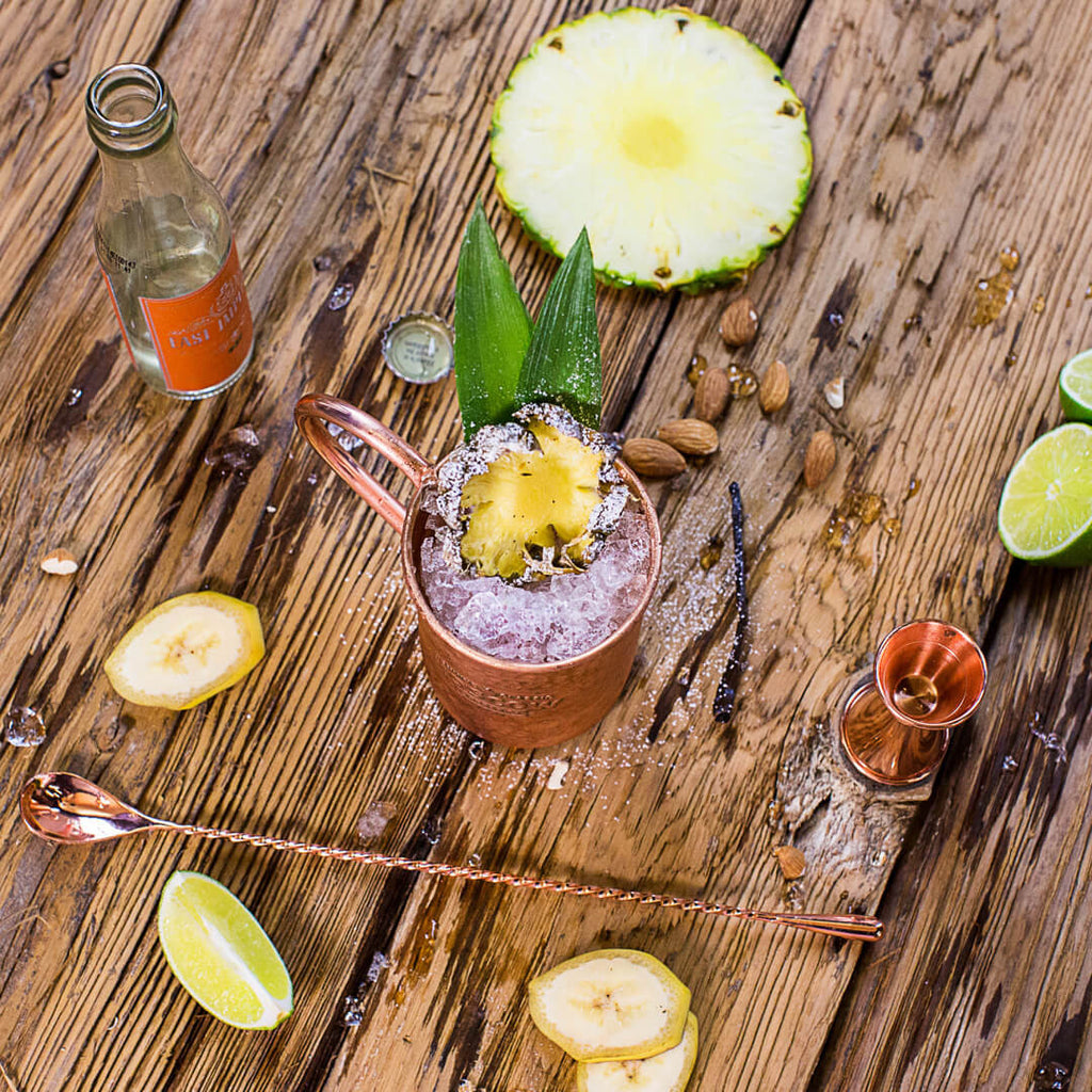 A classic Moscow Mule is dressed up when served in a beautiful 100% copper mug and garnished with fresh pineapple.