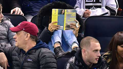 Sarah Jessica Parker reads a book at a hockey game.
