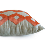 Handmade ivory throw pillow with orange ikat embroidery