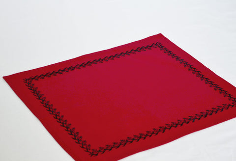 Red place mats with jet black embroidery.