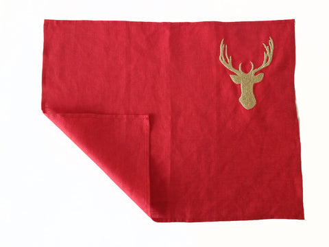 Red linen place mats with gold deer embroidery.