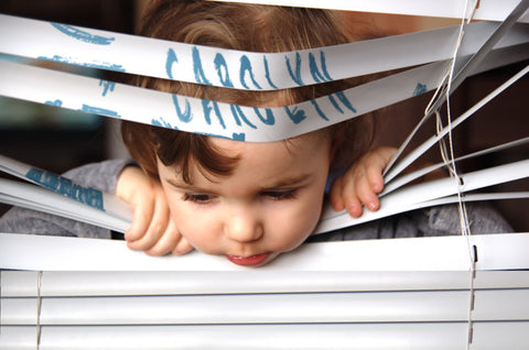 Child Glancing Through a Venetian Blind / 100324