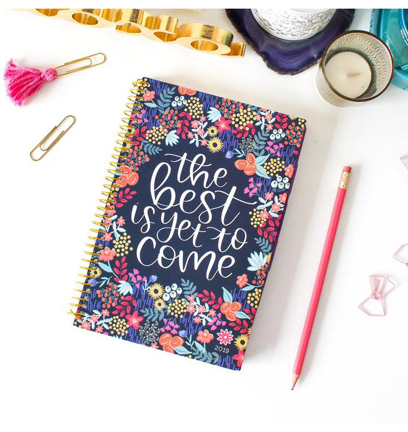 Bloom's The Best Is Yet To Come 2019 Soft Cover Daily Planner On a White Desk with Stationery