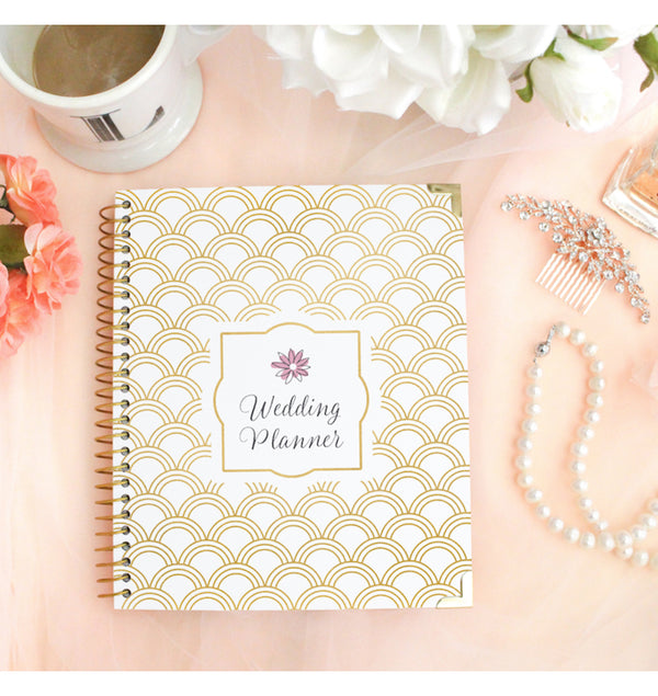 Bloom Gold Scallops Hardcover Wedding Planner Undated on a Pinkish Desk