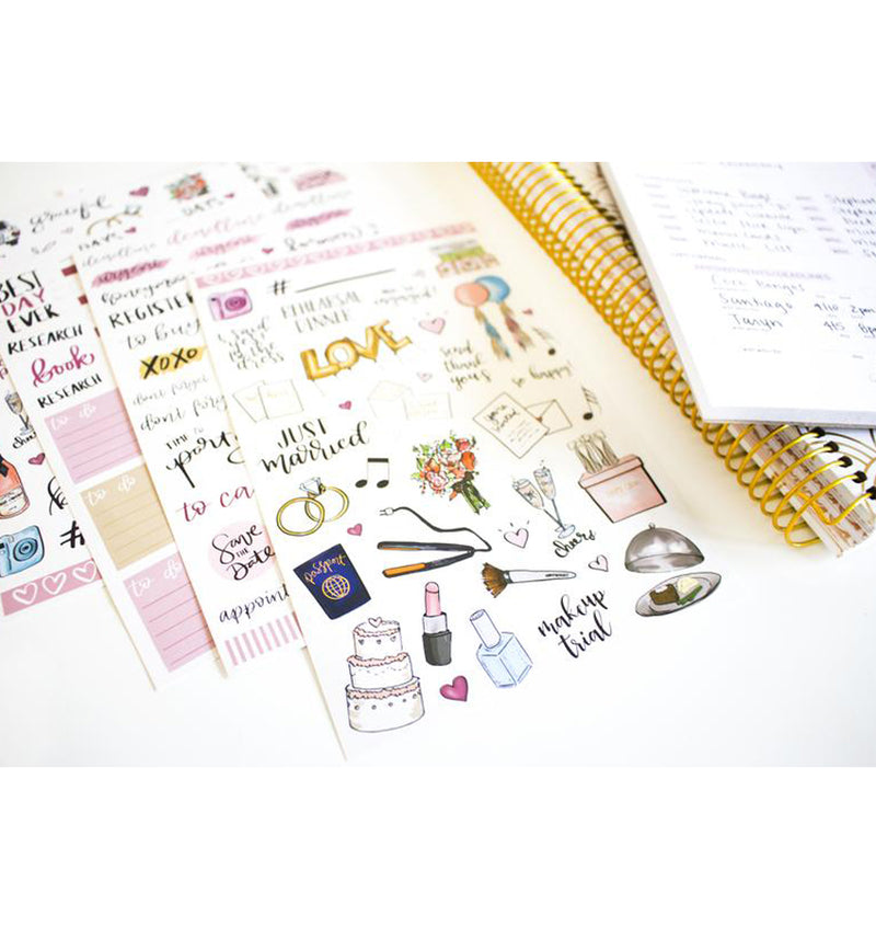 Bloom's Wedding Planner Sticker Sheets Lying Beside a Planner with Binder