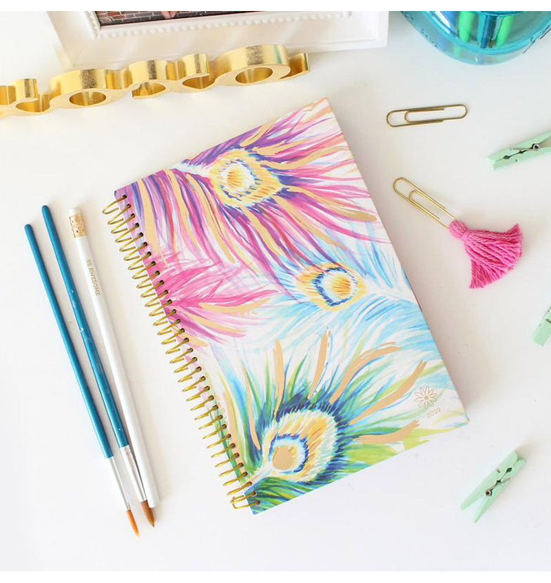 Bloom Peacock Feathers 2019 Soft Cover Daily Planner on a Desk