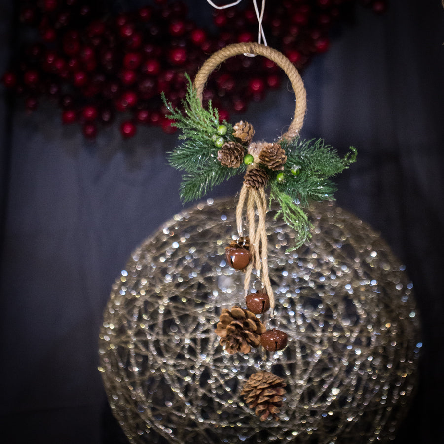 Pinecone, greenery, bells and rope doorknob hanger