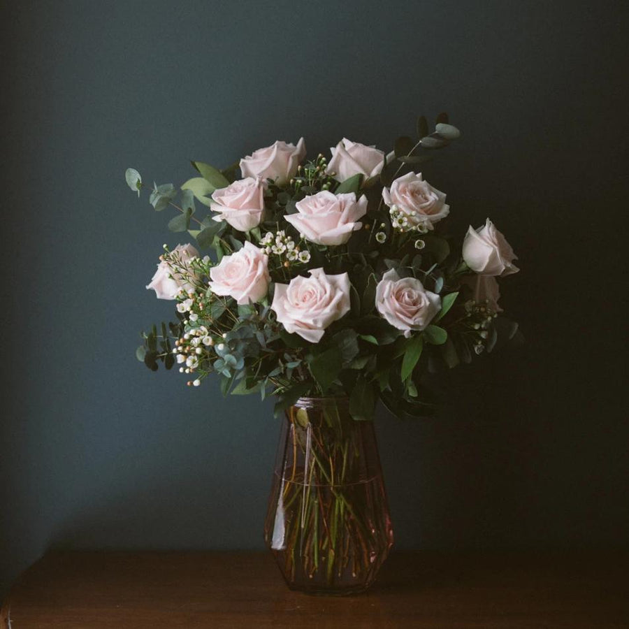 One dozen pink roses in vase