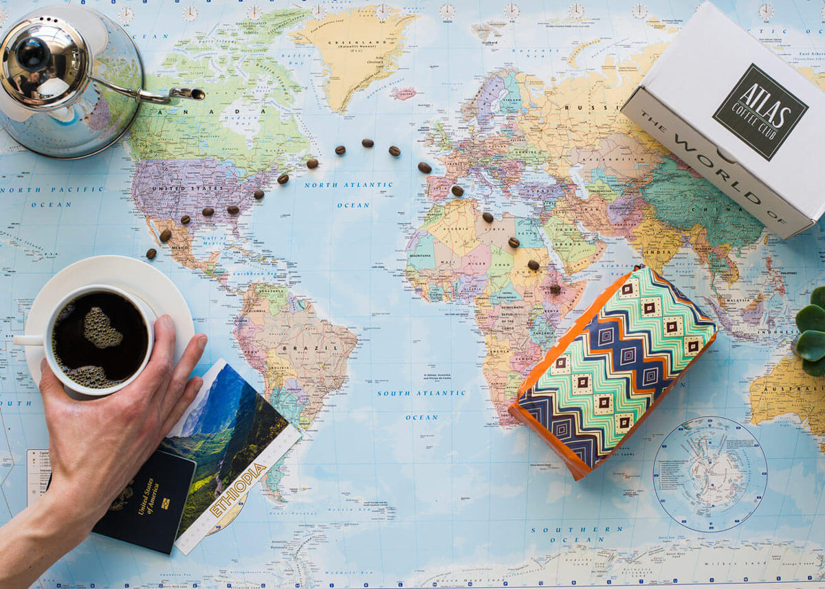 A coffee cup and a printed coffee bag sitting on top of a map, with coffee beans connecting a line between the two.
