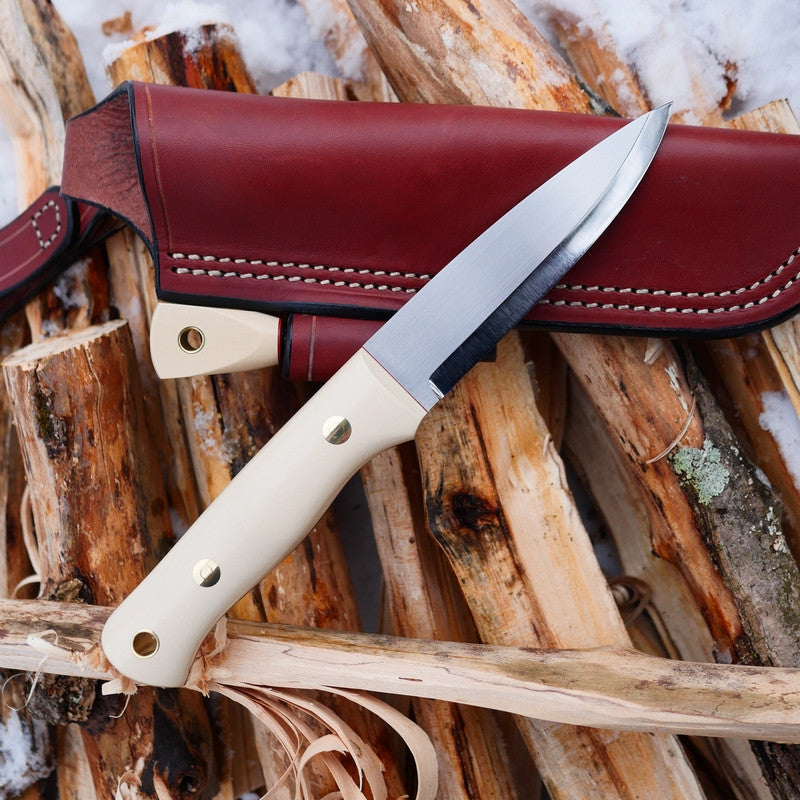 Adventure Sworn Classic bushcraft knife with a scandi grind and ivory paper micarta handle scales