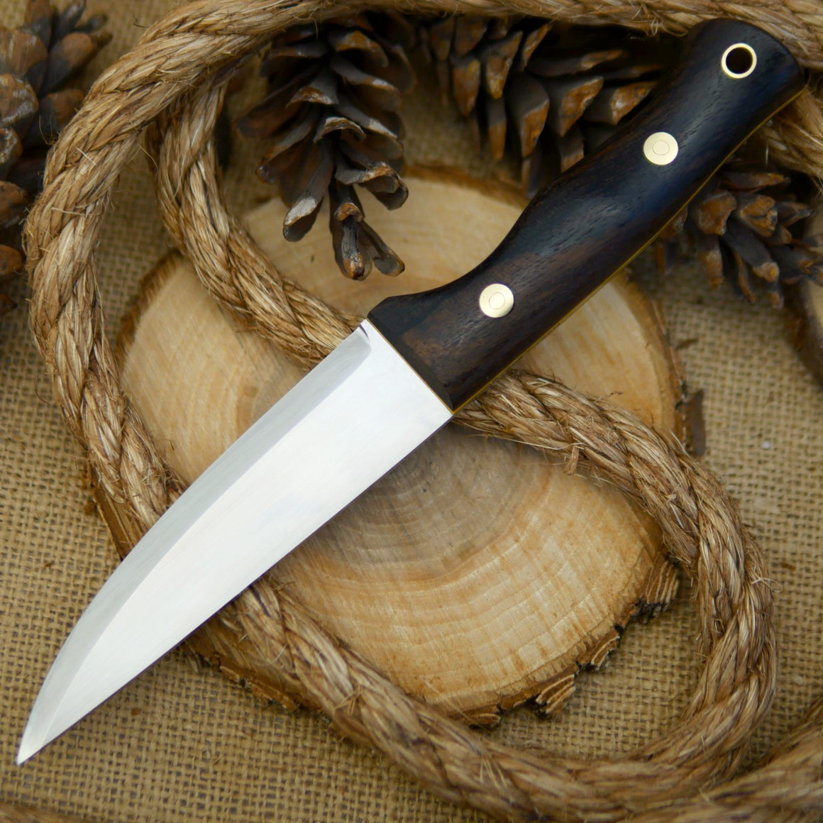An Adventure Sworn Tradesman bushcraft knife with ziricote handle scales.