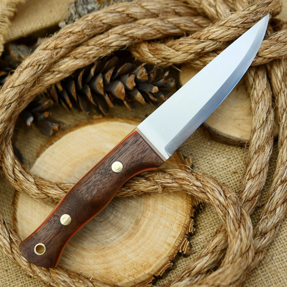 An Adventure Sworn bushcraft knife with walnut handle scales and thick bone linen micarta and thin red liners.