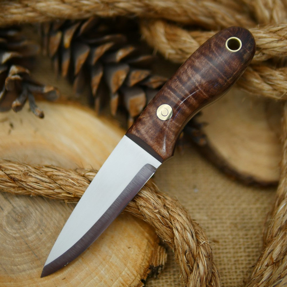 An Adventure Sworn Walker Bushcraft Knife with dark brown curly maple handle scales and thick maroon liners.