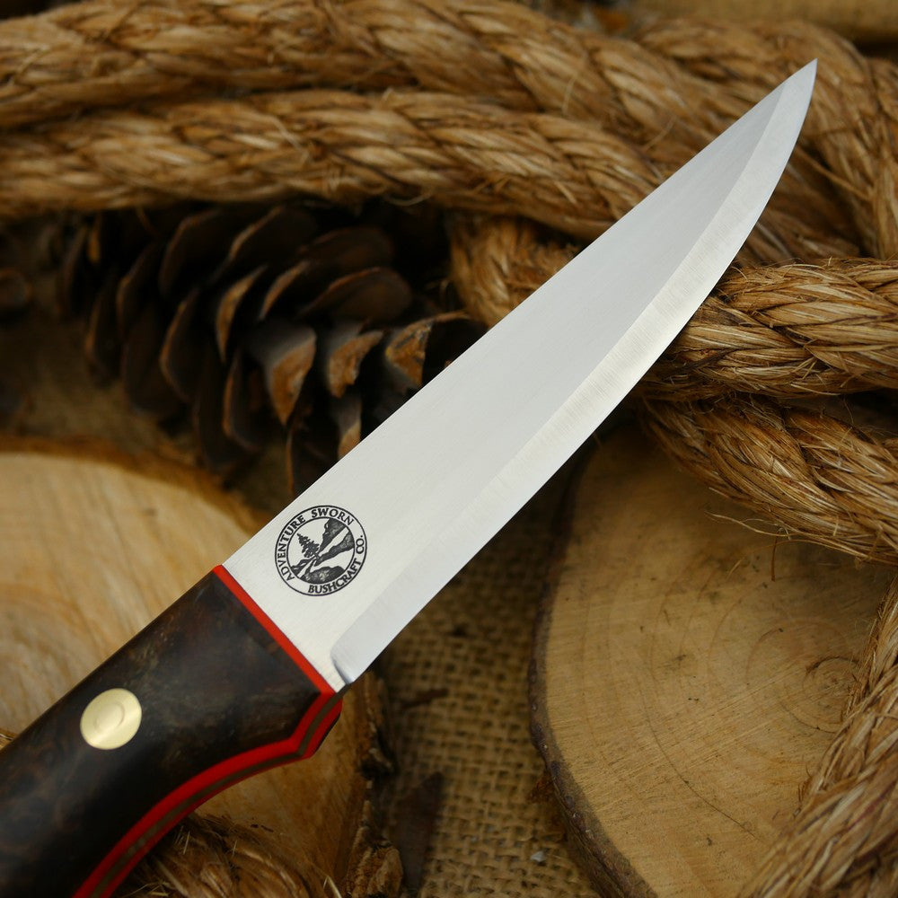 A Voyageur bushcraft knife with stabilized maple burl and hunter orange g10 liners.