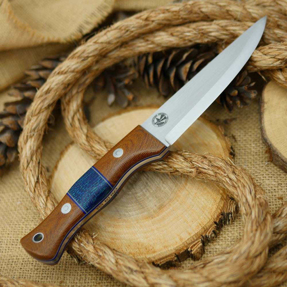 An Adventure Sworn bushcraft knife with natural brown canvas micarta handle scales and navy blue burlap spacer.