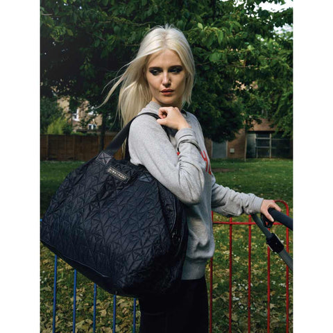 Woman carrying Tiba + Marl Raf Black Holdall Changing bag from Yellow Lolly