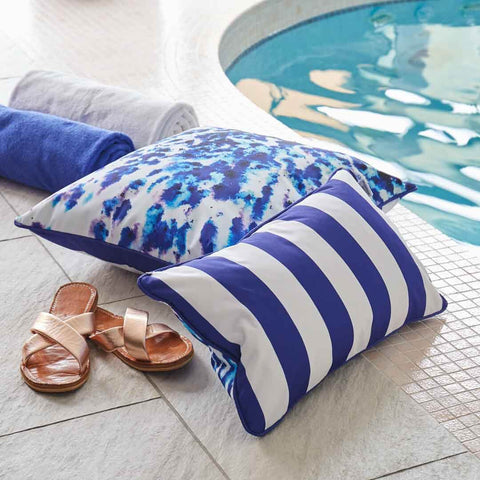 Outdoor Cushion in Mesmerise Print with blue stripe reverse by the pool by Penelope Hope