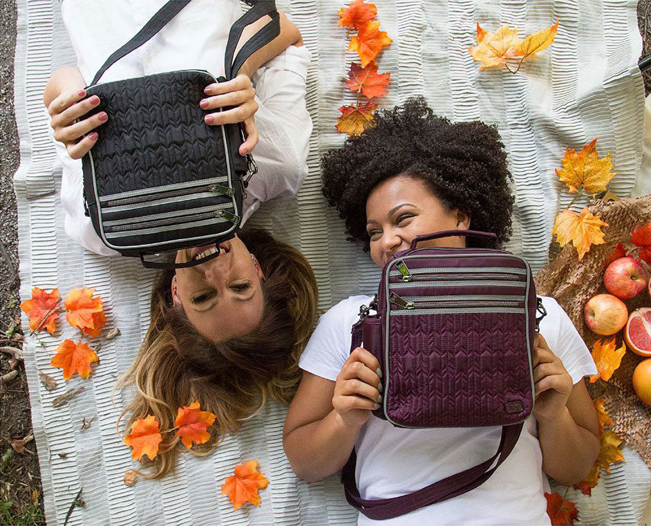 Women holding Boxcar cross body bags laying on autumn setting