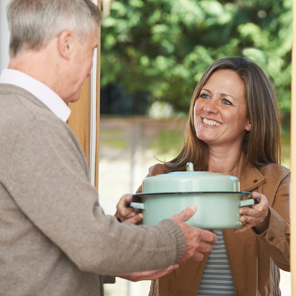 Woman handing elderly man food