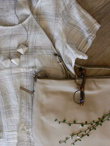flat lay of Chocolat garment, Elk bag and necklace, available at Hall Greytown
