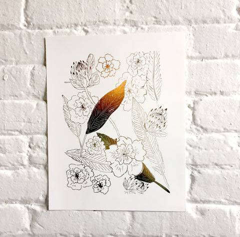 Photo of a Botanical art print with floral pattern in gold foil against a white brick wall