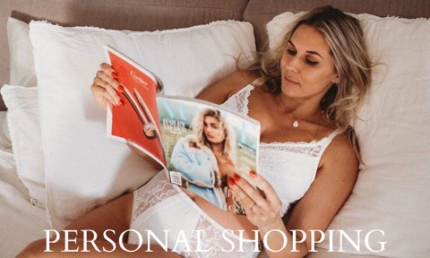 Women laying on bed holding magazine in white undergarments