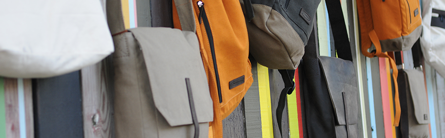 CAUSEGEAR products hanging on colorful fence. Tote, taupe canvas messenger bag, orange sport bag, charcoal urban pack, leather messenger bag.