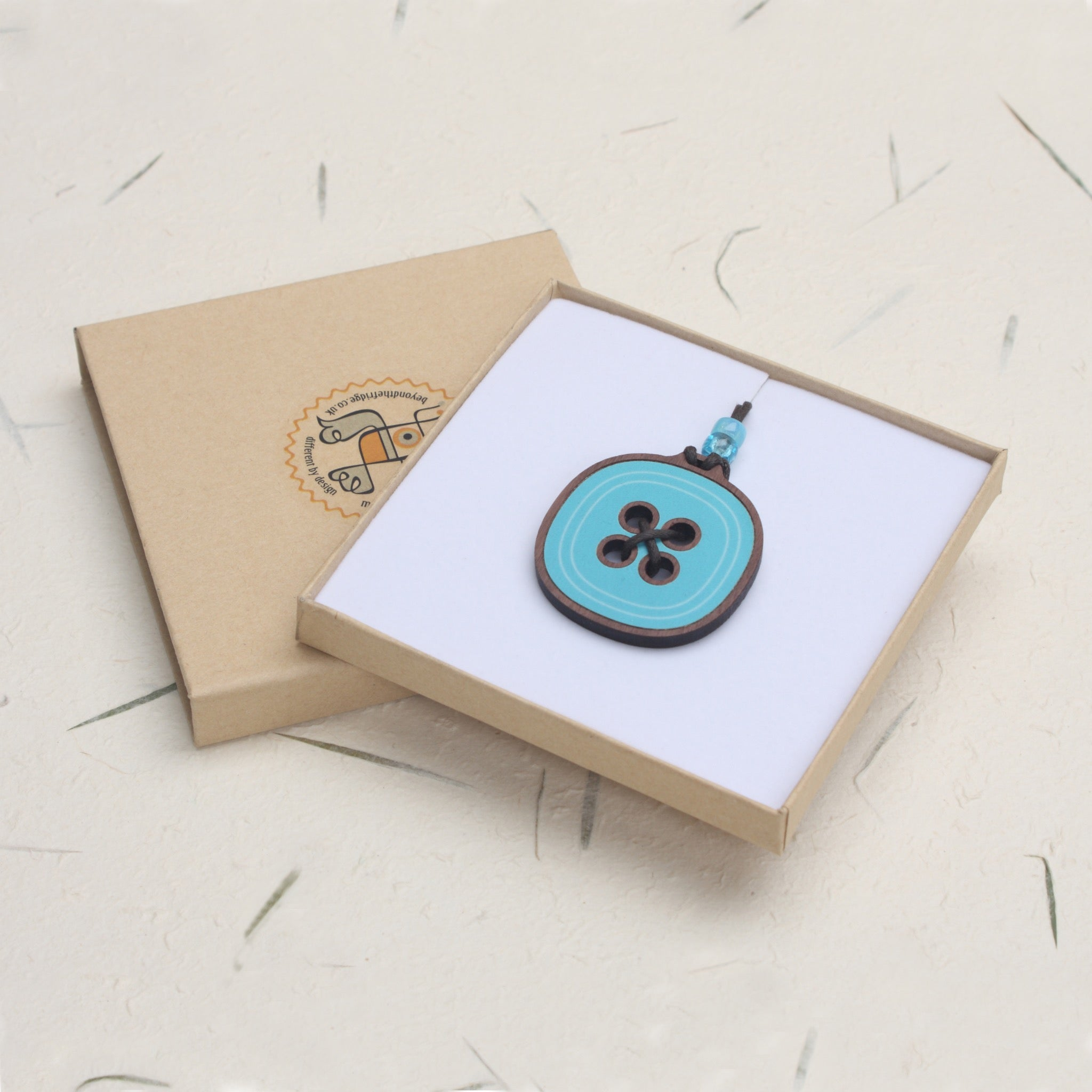 button design wooden pendant in blue presented in a gift box