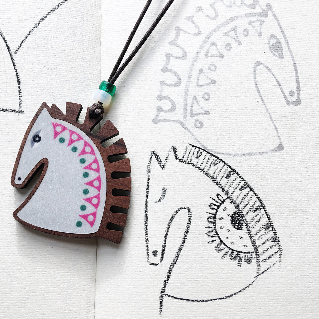 horse pendant with sketches for design