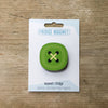 Green button design fridge magnet on pack by Beyond the Fridge