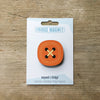 Orange button design fridge magnet on pack by Beyond the Fridge