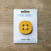 Yellow button design fridge magnet on pack by Beyond the Fridge