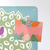 coloured birds in a tree design magnetic notice board with a postcard attached with a watering can fridge magnet