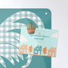 gingham cockerel design magnetic notice board with a postcard attached with a cactus fridge magnet