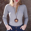 model wearing sunburst design walnut pendant necklace