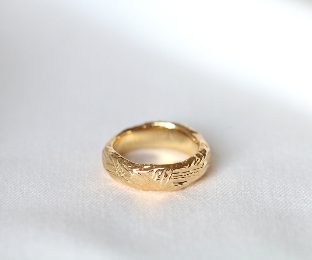 A solid gold thumb ring with etched texture, handmade in Islington.
