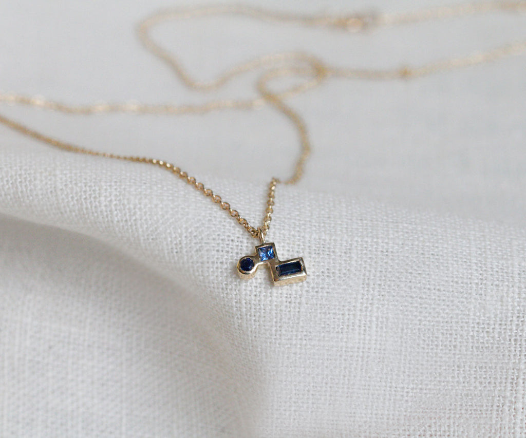 blue sapphire cluster necklace with brilliant cut, princess cut and baguette cut sapphire stones, handmade in 9ct yellow solid gold, handcrafted in London, UK, part of Sapphire collection, Maya Magal luxury jewellery brand