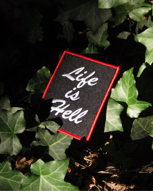 "Official ""NO FUN®"" patch which reads ""LIFE IS HELL"". The patch features white, embroidered text with a red embroidered edge.  Photo shows the patch in its natural habitat, nature."