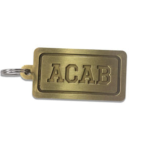"Photo show the brass ""ACAB"" keychain. The font is engraved in the brass tag with a thick border which is also engraved."