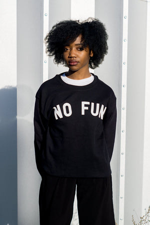 "Photo of a female model wearing the original ""NO FUN®"" logo crewneck sweater. The sweater is black and features large white text that reads ""NO FUN®""."