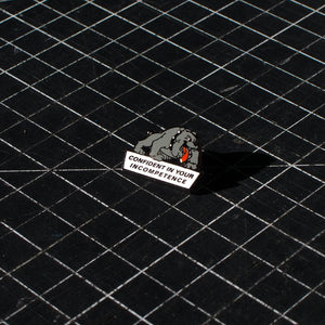 "The No Fun Press ""Confident Dog"" lapel pin on a black cutting-mat."