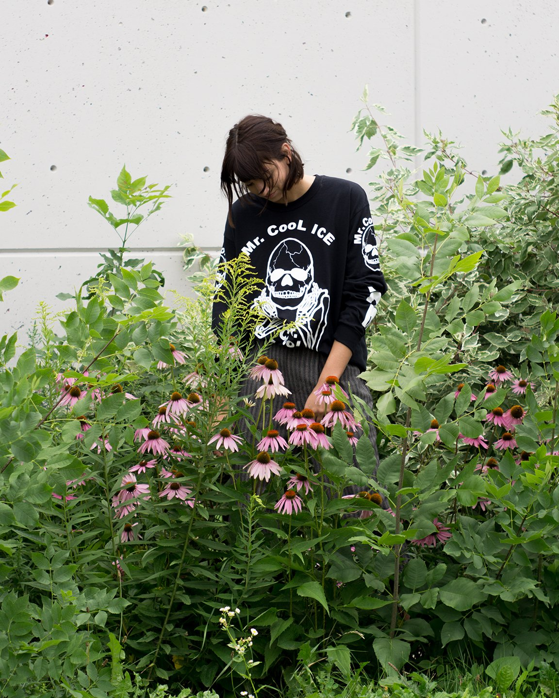 "The No Fun Press ""Mr. Cool Ice"" longsleeve shirt worn by a young woman, standing in a garden."