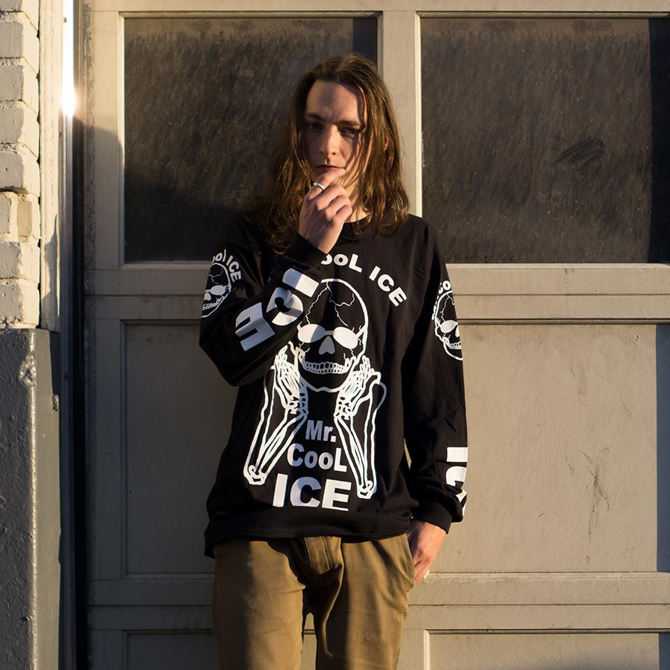 "The No Fun Press ""Mr. Cool Ice"" longsleeve shirt worn by a young man, standing in front of a garage."